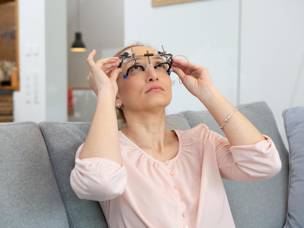 OkuStim therapie use: a woman puts on the OkuSpex