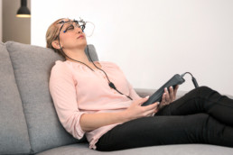 OkuStim therapy use: a woman reclines on a sofa during therapy